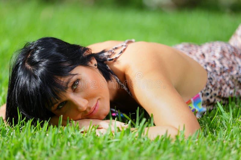 Attraktive Frau, die auf Gras legt stockbild