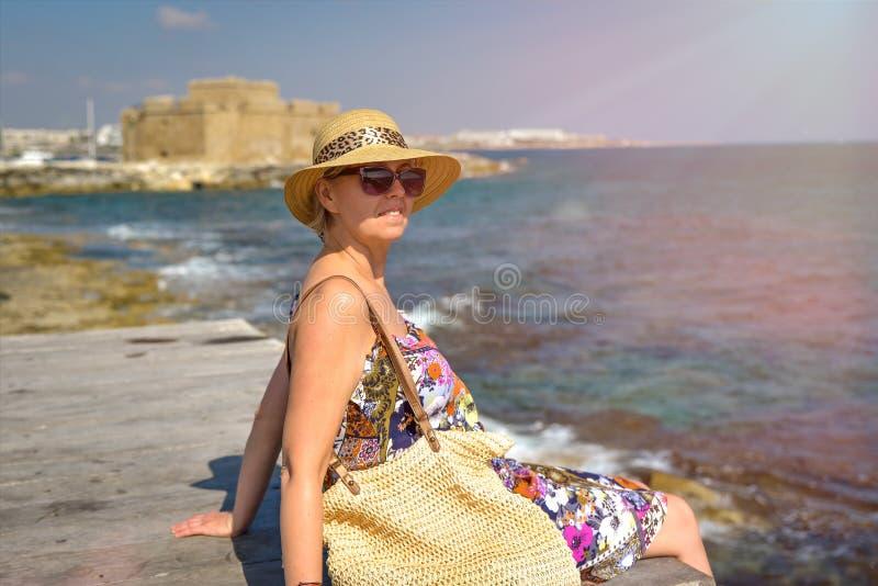 Attraktive Frau, die auf Pier sitzt stockbild