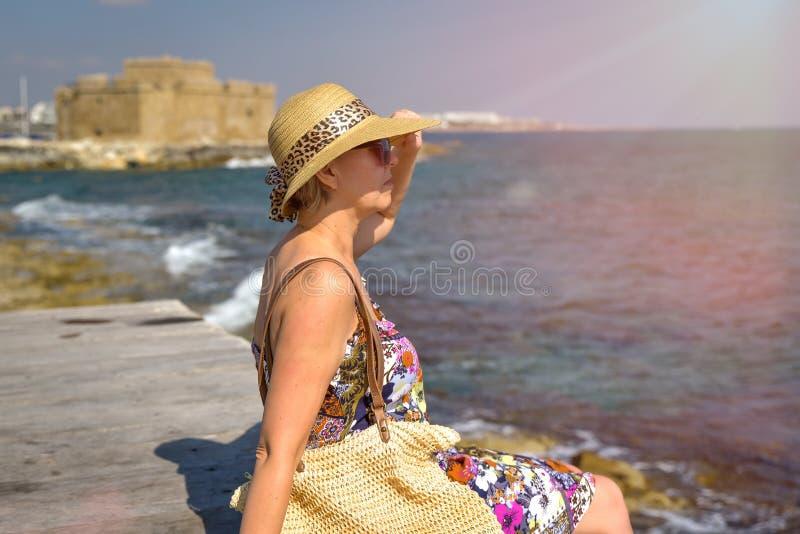 Attraktive Frau, die auf Pier sitzt lizenzfreie stockfotografie