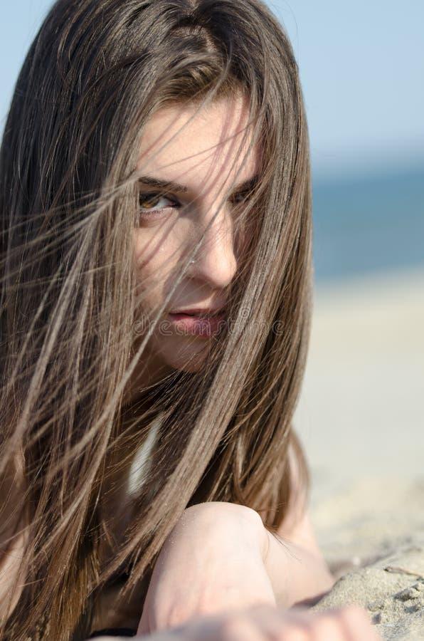 Attraktive Frau, die auf Sandabnutzungsbikini liegt stockbilder