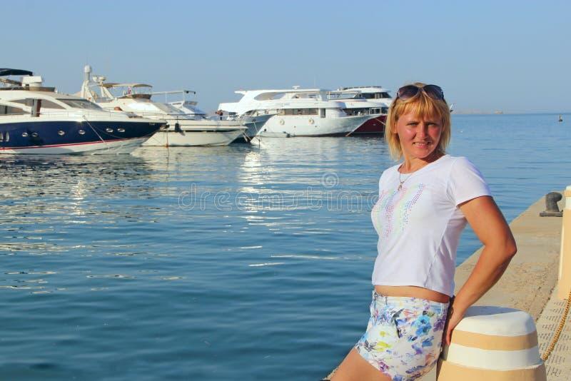 Attraktive Frau, die auf Seeseite sich entspannt Hübsches Mädchen, das nahe Seehafen stillsteht stockbild