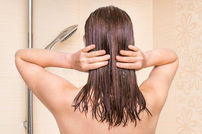 Attraktive Frau, die Conditioner auf ihrem Haar im Badezimmer anwendet stockfotografie