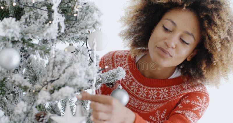 Attraktive Frau, die den Baum für Weihnachten vorbereitet stockbild