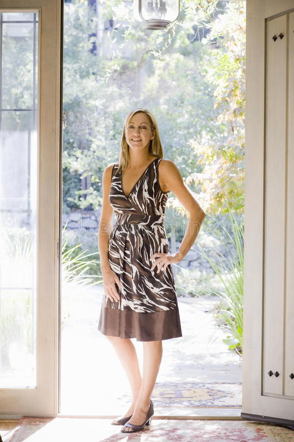 Attraktive Frau, die in der Tür steht stockbilder