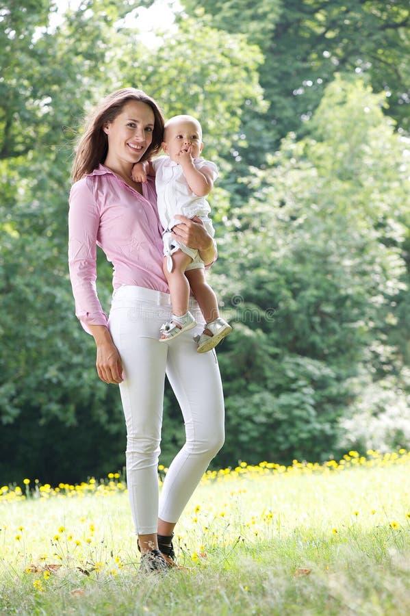 Attraktive Frau, die draußen Baby hält lizenzfreies stockbild
