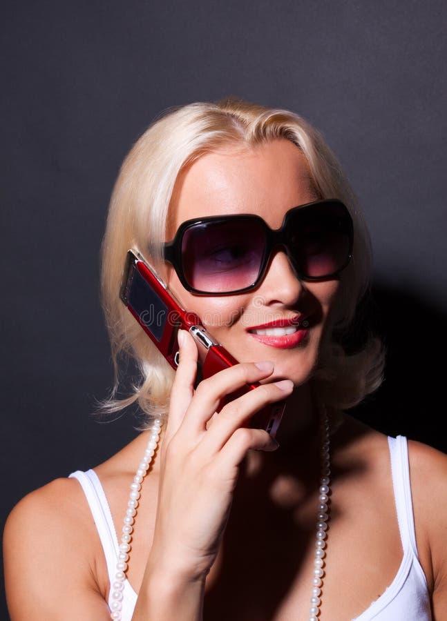 Attraktive Frau, die durch Mobile und das Lächeln benennt stockfotografie