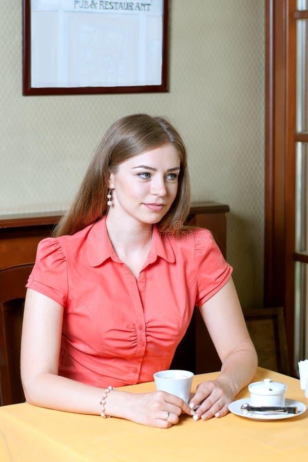 Attraktive Frau, die in einem Restaurant mit einem Tasse Kaffee sitzt stockfotos