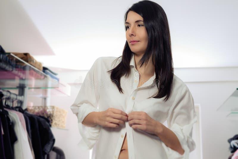 Attraktive Frau, die in einer Umkleidekabine ankleidet stockbild