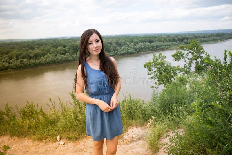 Attraktive Frau, die gegen den Hintergrund des Waldes aufwirft stockfotos