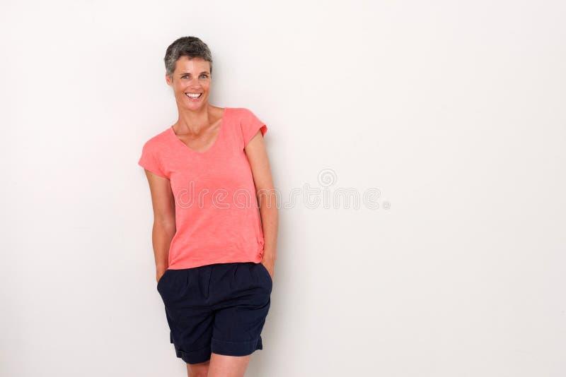 Attraktive Frau, die gegen weiße Wand lacht stockfoto