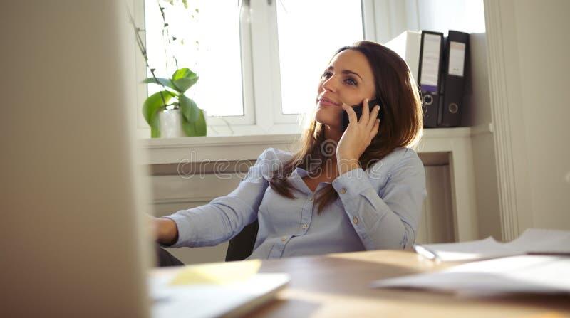 Attraktive Frau, die am Handy von ihrem Schreibtisch spricht lizenzfreies stockbild