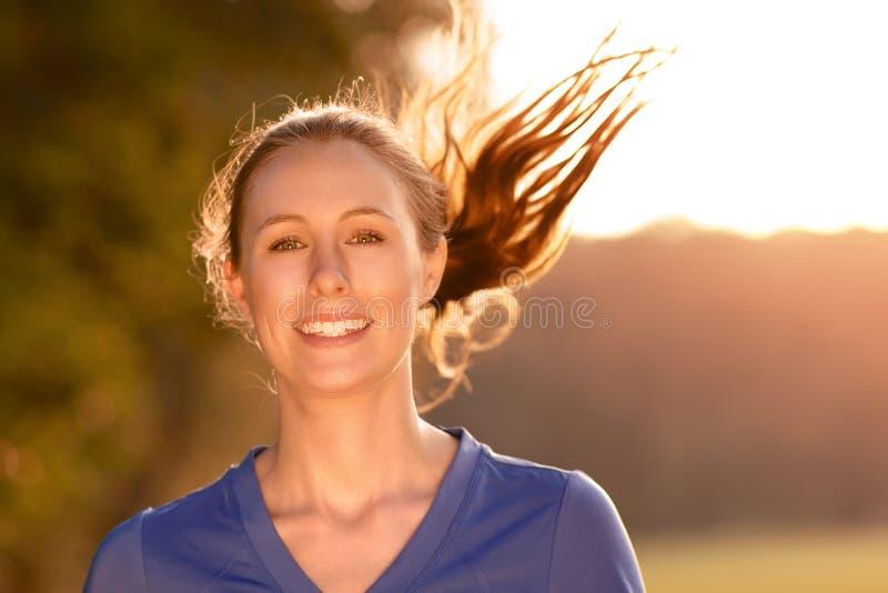 Attraktive Frau, die heraus in glühendem Licht trainiert lizenzfreie stockfotografie