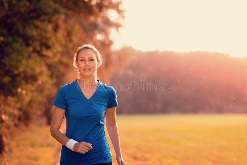 Attraktive Frau, die heraus in glühendem Licht trainiert stockfoto