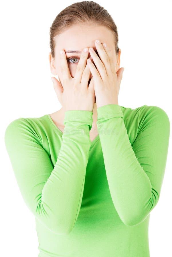 Attraktive Frau, die ihr Gesicht mit beiden Händen bedeckt. stockbilder