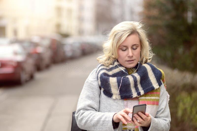 Attraktive Frau, die ihr Mobile in einer Straße überprüft lizenzfreie stockfotografie