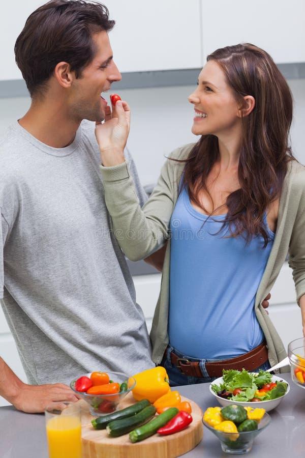 Attraktive Frau, die ihre Ehemannkirschtomate einzieht stockbild