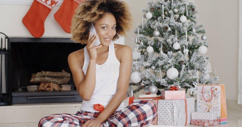 Attraktive Frau, die ihre Freunde am Weihnachten anruft stockfoto