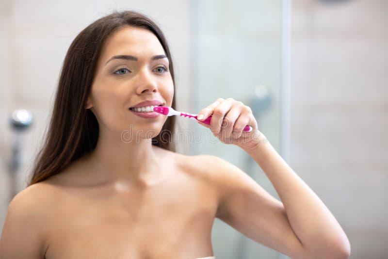 Attraktive Frau, die ihre Zähne putzt lizenzfreie stockfotos