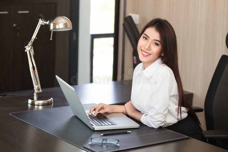 Attraktive Frau, die im Büro auf Laptop arbeitet lizenzfreies stockfoto