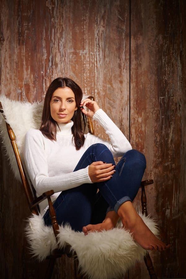 Attraktive Frau, die im Lehnsessel sitzt lizenzfreie stockfotos