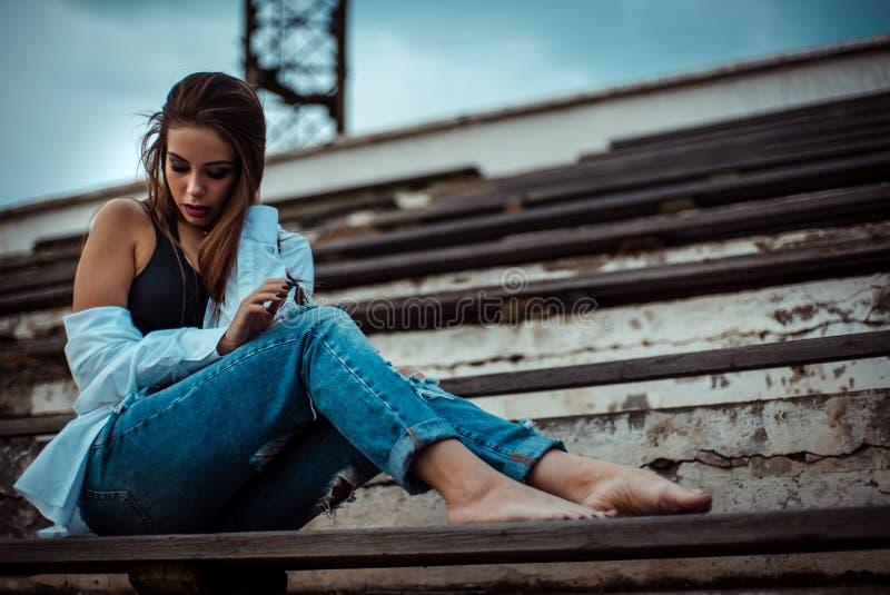 Attraktive Frau, die mit bloßen Füßen im Stadion sitzt Sie trägt ein Hemd und Jeans stockfoto