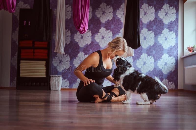Attraktive Frau, die mit ihrem netten Hund beim Sitzen auf Boden im Yogafitness-club spielt stockfotografie