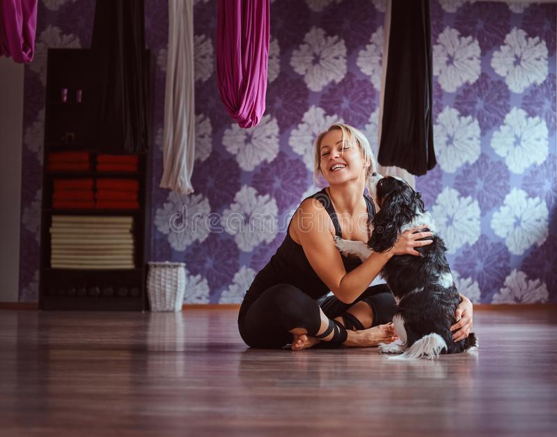 Attraktive Frau, die mit ihrem netten Hund beim Sitzen auf Boden im Yogafitness-club spielt lizenzfreie stockfotografie