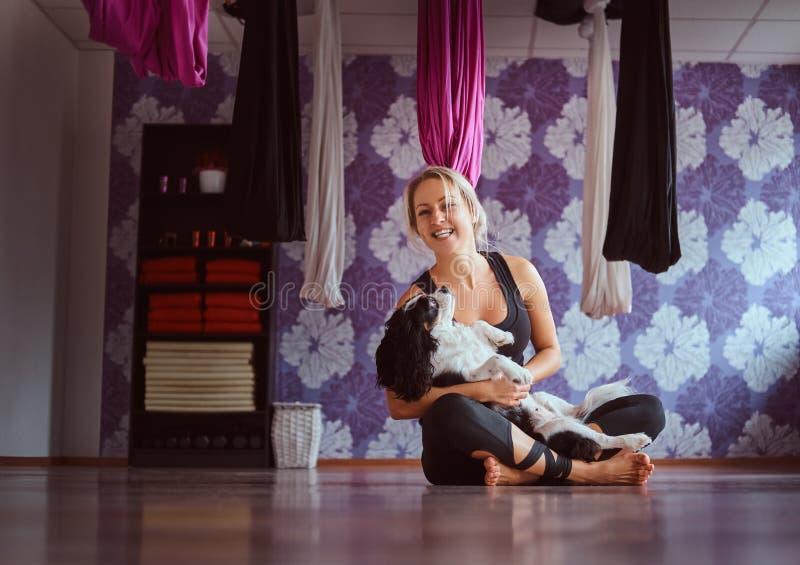 Attraktive Frau, die mit ihrem netten Hund beim Sitzen auf Boden im Yogafitness-club spielt lizenzfreies stockbild