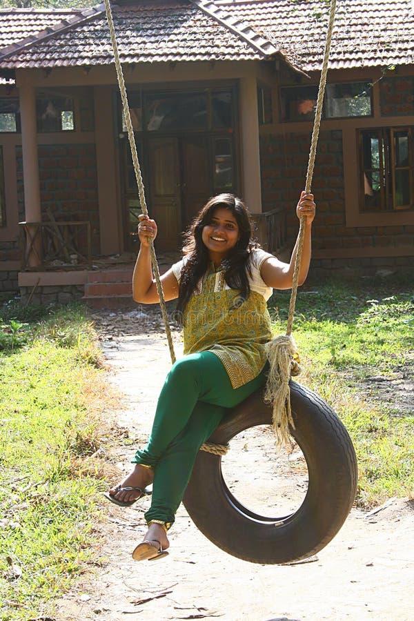 Attraktive Frau, die Spaß auf Gummireifenschwingen hat lizenzfreie stockfotos