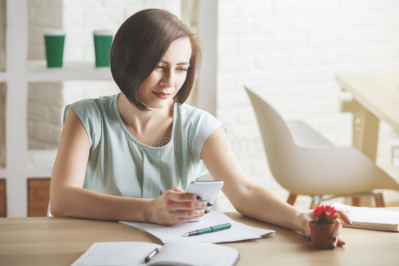 Attraktive Frau, die Telefon im Büro verwendet stockfotografie