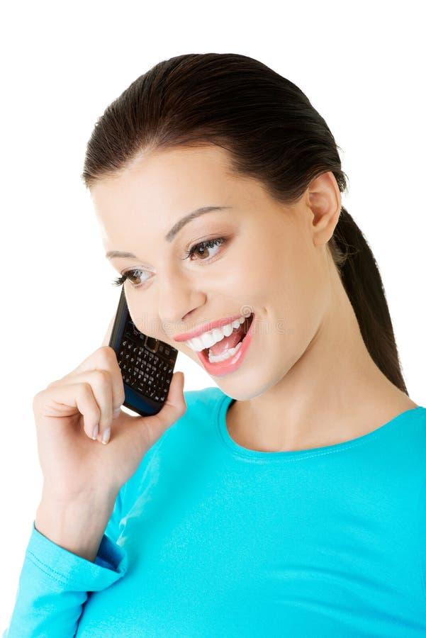 Attraktive Frau, die am Telefon spricht. lizenzfreie stockbilder