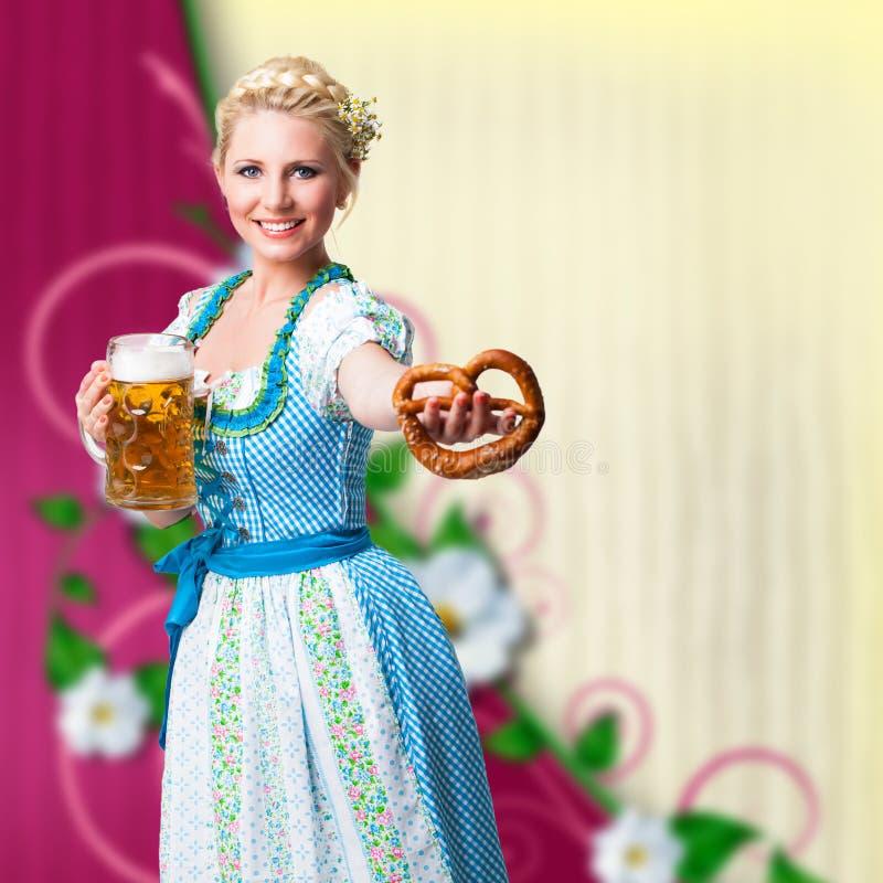 Attraktive Frau in einem Dirndl mit Bier und Brezel stockfotos