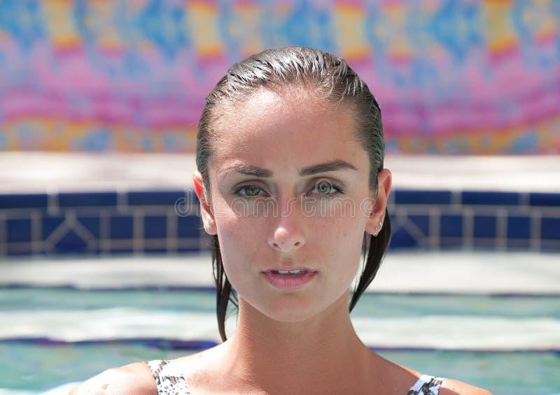 Attraktive Frau in einem Pool, das einen Badeanzug trägt stockfoto