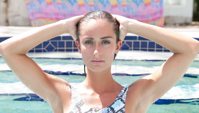 Attraktive Frau in einem Pool, das einen Badeanzug trägt stockbild