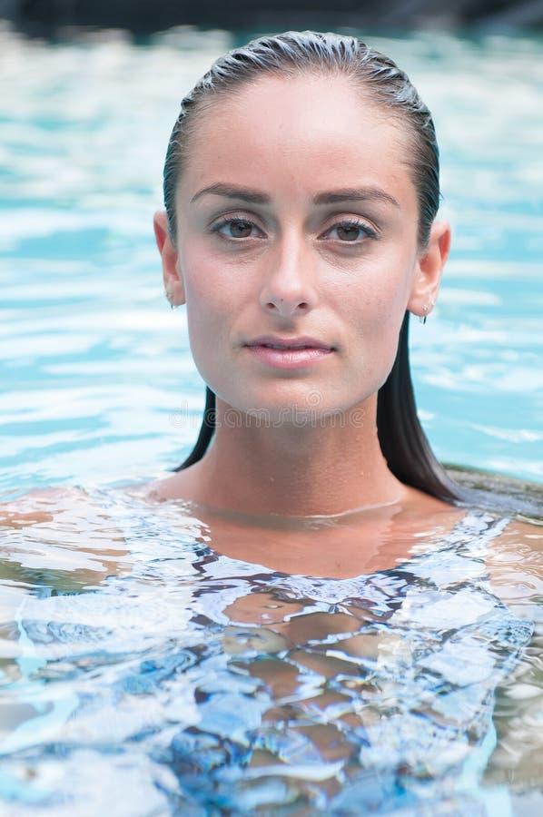 Attraktive Frau in einem Pool, das einen Badeanzug trägt stockbilder
