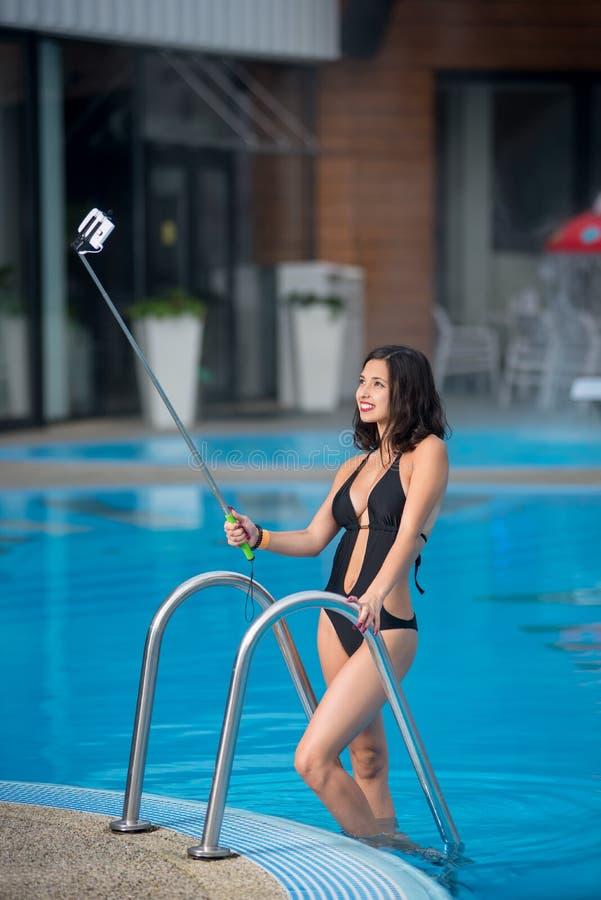 Attraktive Frau in einem schwarzen Bikini, der gegen den Swimmingpool, selfie Foto mit selfie Stock auf Luxus-Resort machend aufw stockbilder