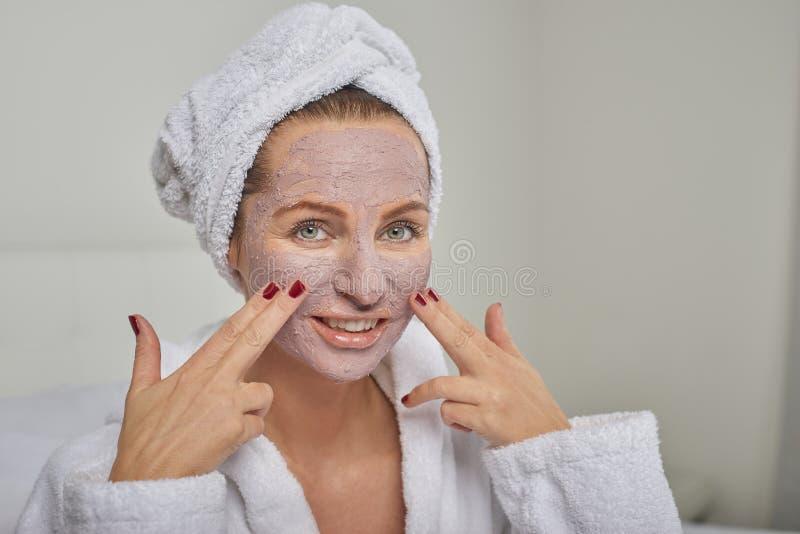Attraktive Frau in einer weißen towelling Robe, die eine Gesichtsmaske anwendet stockbild