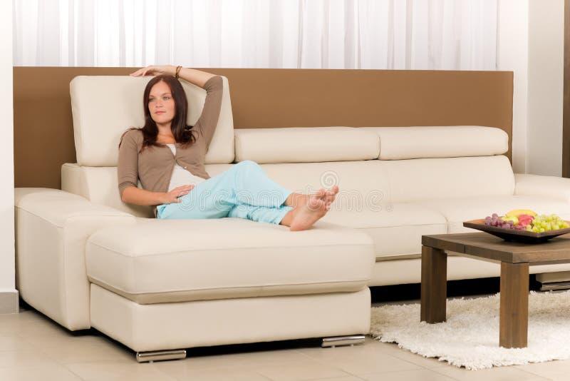 Attraktive Frau entspannen sich Wohnzimmerledersofa stockbilder