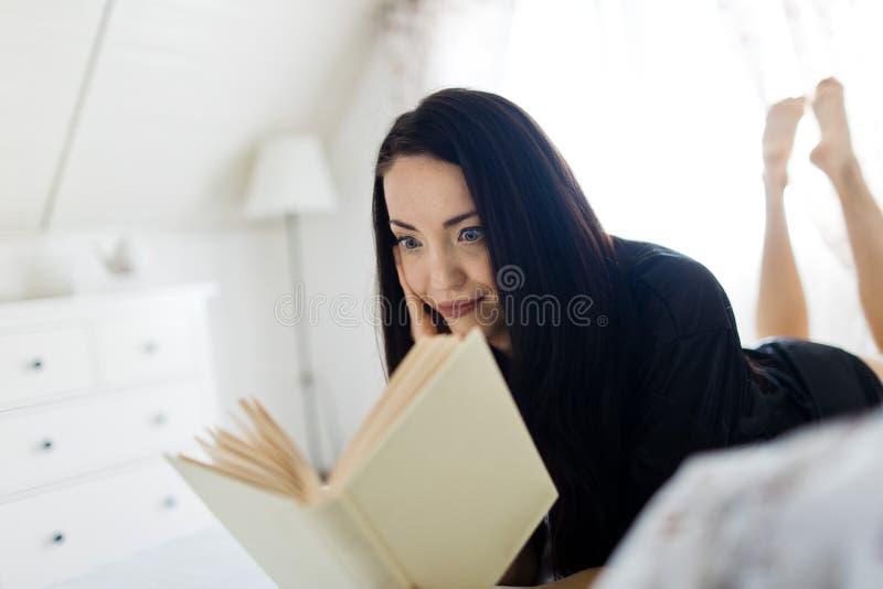 Attraktive Frau gekleidet im schwarzen sexy Sleepwear, der auf Bett legt stockbild