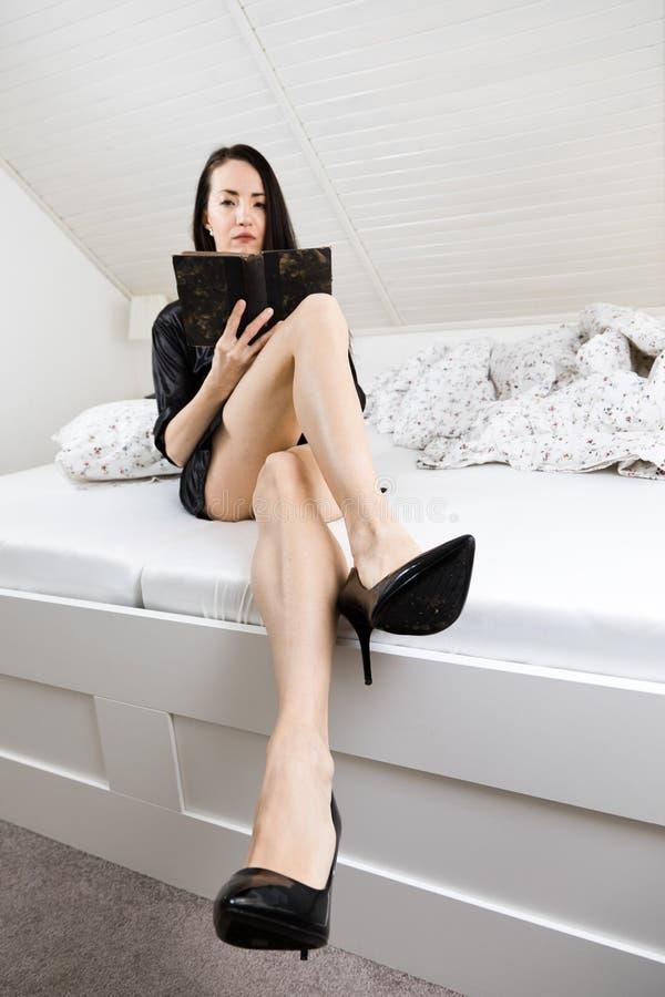 Attraktive Frau gekleidet im schwarzen sexy Sleepwear, der morgens auf Bett und Ablesenbuch sitzt lizenzfreie stockfotos