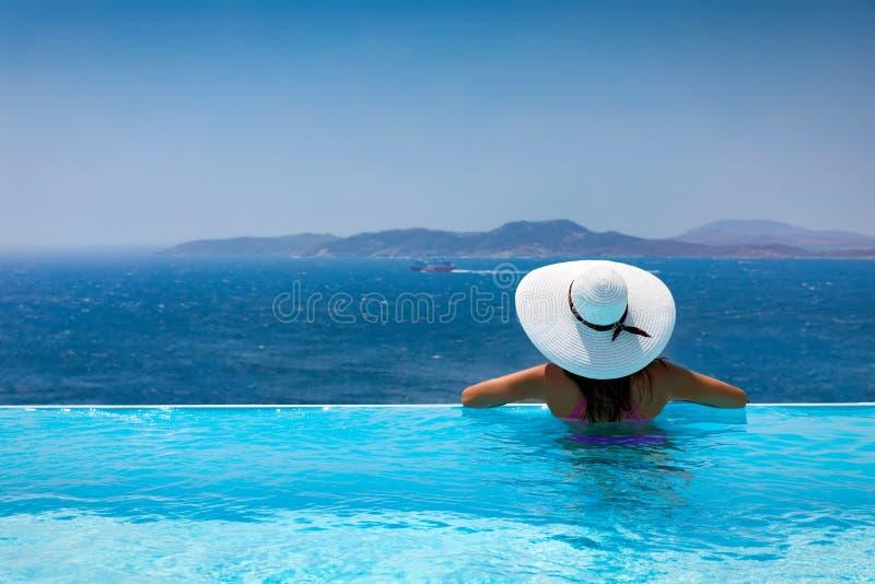 Attraktive Frau genießt die Ansicht vom Pool zum Mittelmeer lizenzfreie stockfotografie