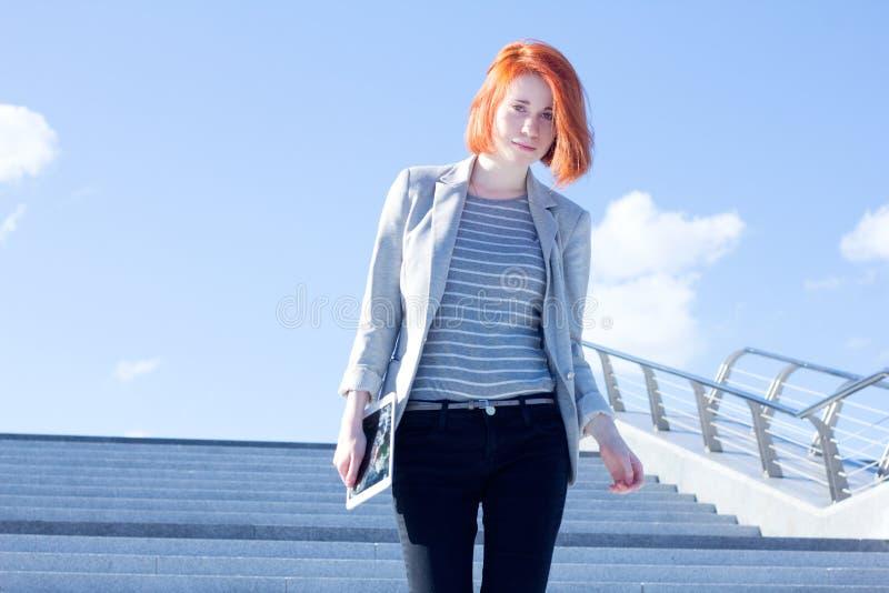 Attraktive Frau hinunter die Treppe mit Tablette gegen den Himmel stockbild
