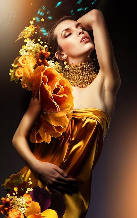 Attraktive Frau im gelben Kleid mit Schmuck und Blumen stockfotografie
