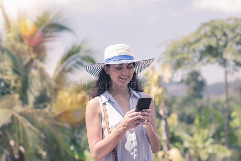 Attraktive Frau im Hut online verständigend mit Zellintelligentem Telefon über tropischem Forest View Young Girl Chatting stockbild