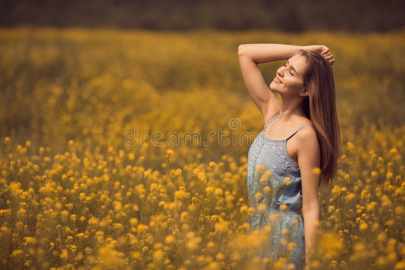 attraktive Frau im Kleid am Blumenfeld lizenzfreie stockbilder
