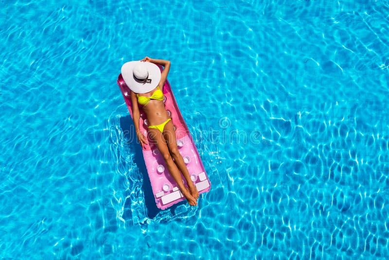 Attraktive Frau im Pool mit einer sich hin- und herbewegenden Matratze lizenzfreie stockfotografie