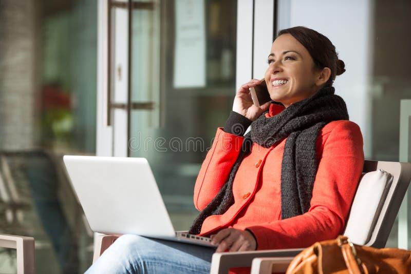 Attraktive Frau im roten Mantel, der einen Anruf hat lizenzfreies stockbild
