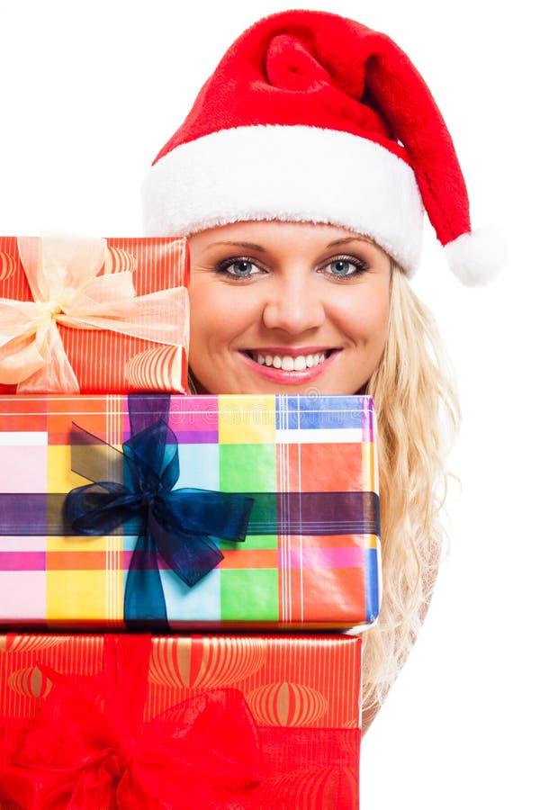 Attraktive Frau im Sankt-Hut mit Weihnachtsgeschenken lizenzfreie stockfotos