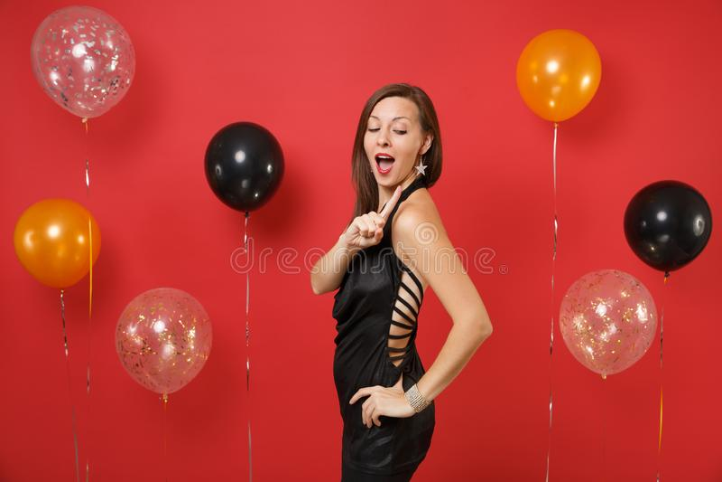 Attraktive Frau im schwarzen Kleid feiernd, schauend hinter und zeigen Finger auf Schmuck auf hellem rotem Hintergrund lizenzfreie stockbilder