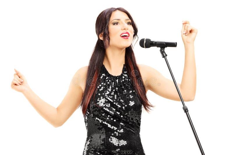 Attraktive Frau im schwarzen Kleid singend lizenzfreies stockbild